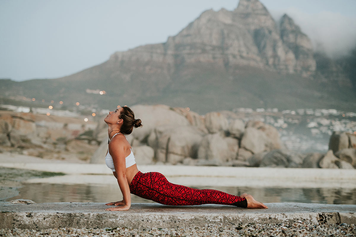 Woman doing cobra yoga pose on Cape Town beach